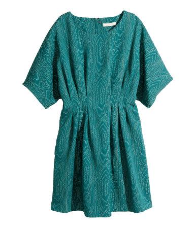 Een knielange, getailleerde jurk van jacquardgeweven kwaliteit met structuur. De jurk heeft een ruimvallend lijfje, deels ingestikte plooien in de taille, korte mouwen, steekzakken en een blinde ritssluiting achter. Ongevoerd.
