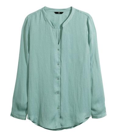 Een blouse van satijn met dessin. Het model is rond gesneden aan de onderkant en heeft een opstaand kraagje, een V-hals, lange mouwen en een iets langer achterpand. Knoopsluiting voor en onder aan de mouwen. In lichtgroen.