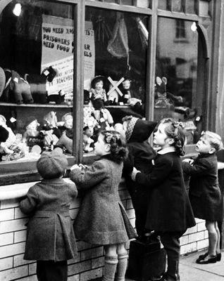 Kerstmis in de oorlog. Kinderen kijken verlangend naar het speelgoed in de etalage.