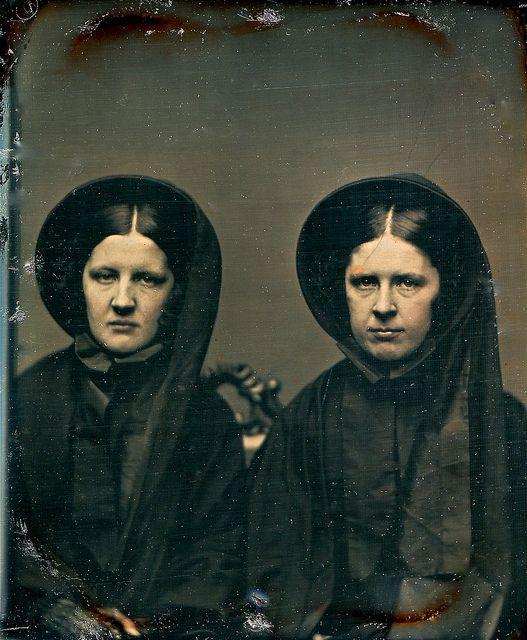 Een aan elkaar identieke tweeling in de rouw. Ook de zwarte rouwkleding komt exact overeen. Cira 1855.